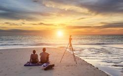 Couple sitting on the sunset beach, in Phuket Thailand