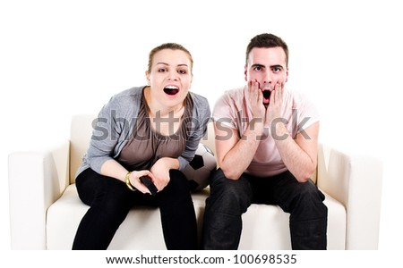 Couple sitting on white sofa and watching scary movie - isolated on white background