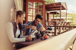 Couple sitting outside a holiday cabin and having coffee. Man pouring coffee in cup with his girlfriend sitting by.
