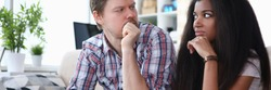 Couple sitting sofa at home looking at each other. Tensions between spouses, unwillingness to compromise. Woman does not agree with decision man. Family troubles over online shopping