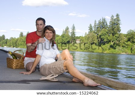 Couple sitting together by a lake with a picnic basket. Horizontally framed photograph
