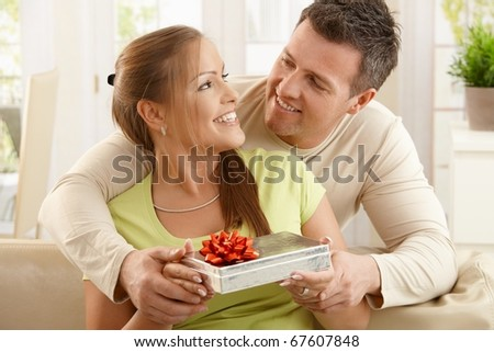 Couple sitting together laughing happily, woman holding present, man holding woman's hands.?