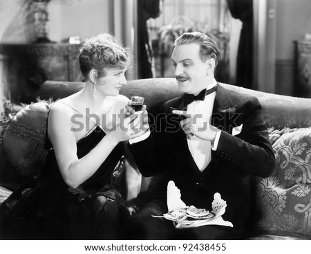 Couple sitting together on a sofa and having a drink