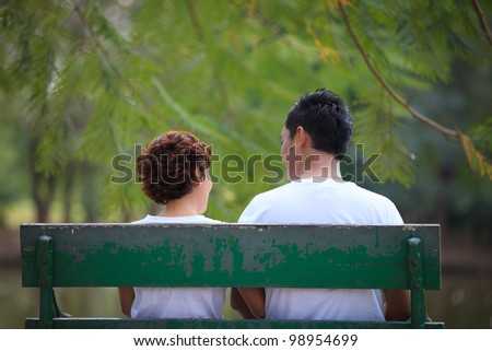 Couple sitting together on park