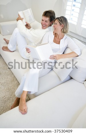 Couple sitting together on white sofa relaxing and reading books