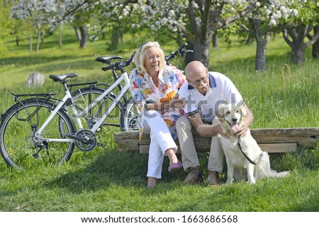 Couple sitting with pet dog in meadow