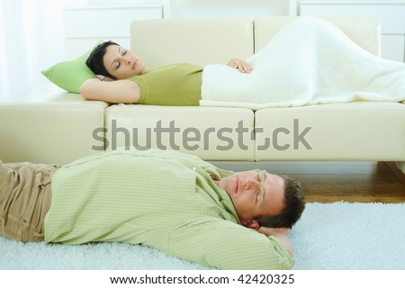 Couple sleeping at home on sofa and on floor.