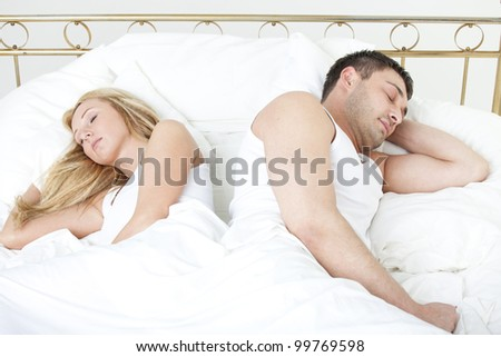 Couple sleeping back on back in bed