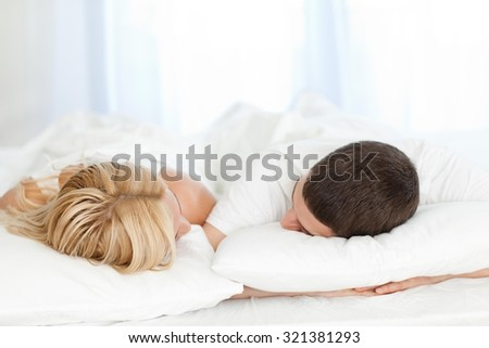Couple sleeping in bed at home.