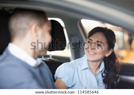 Couple smiling in a car in a car shop