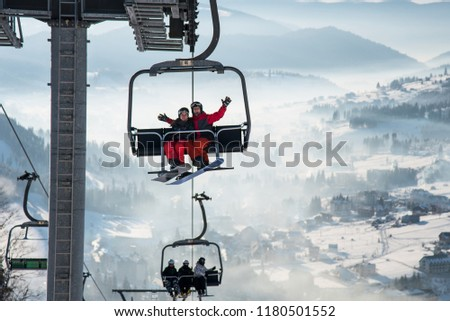Couple snowboarders having fun on a ski lift in ski resort with beautiful background of snow-covered slopes, forests, hills copyspace recreation travelling tourism vacation mountains Bukovel, Ukraine #1180501552
