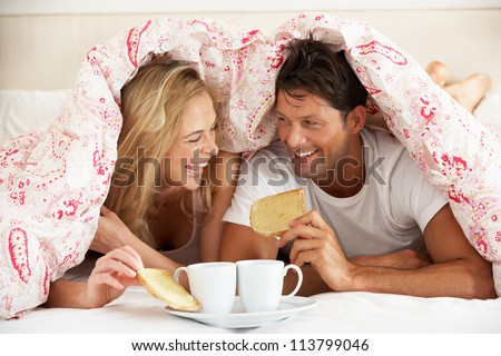 Couple Snuggled Under Duvet Eating Breakfast