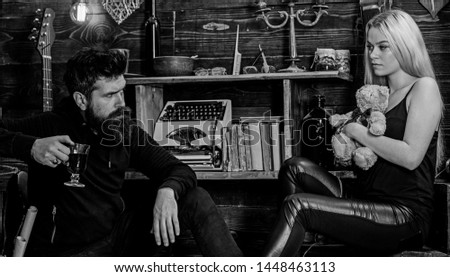 Couple spend romantic evening in gamekeepers house, wooden interior background. Couple in love with teddy bear and mulled wine. Girl and man on relaxed faces enjoy warm atmosphere. Relaxing concept.
