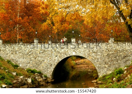 Couple stand on stone bridge and are surrounded by the blazing orange and yellow of an Autumn morning.