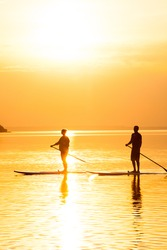 Couple stand up paddle boarding at sunset