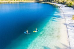 Couple stand up paddle boarding  on Lake Mckenzie, Fraser Island, Queensland, Australia