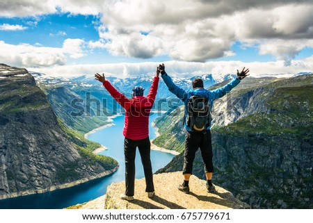 Couple standing against amazing nature view on the way to Trolltunga. Location: Scandinavian Mountains, Norway, Stavanger. Artistic picture. Beauty world. The feeling of complete freedom #675779671