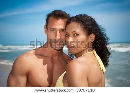 Couple standing at the beach with blue sky in the background