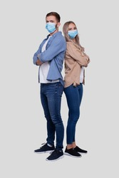 Couple Standing Back to Back Wearing Medical Mask Watching to Camera. Man and Woman, Lovers, Friends, Couple Concept