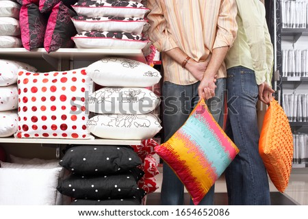 Couple standing beside shelf in shop, carrying orange cushions
