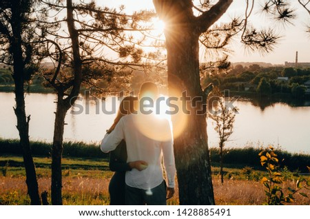 couple standing embraced outside by the lake with sun rays breaking through the tree branches #1428885491