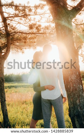 couple standing embraced outside by the lake with sun rays breaking through the tree branches. love concept #1428885839