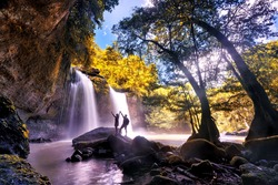 Couple standing hand in hand admiring the beauty of nature.Heo Suwat Waterfall in Khao Yai National Park Famous waterfall park in Thailand . autumn season for  leaves.