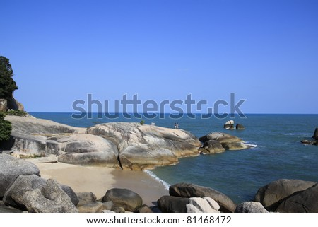 couple standing hand in hand on landmark grandmother and grandfather rocks on lamai beach koh samui in the gulf of thailand