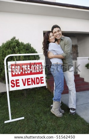 Couple standing in front of house with For Sale sign, portrait