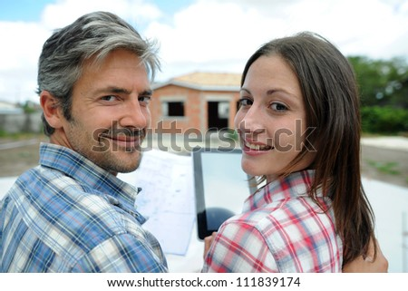 Couple standing in front of their future home - stock photo