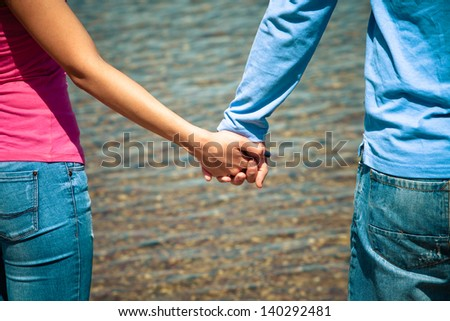 couple standing in front water with hand in hand - stock photo