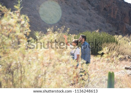 Couple standing in long brown grass on a mountain path, they are pointing up towards the horizon as the sun beats down on them
