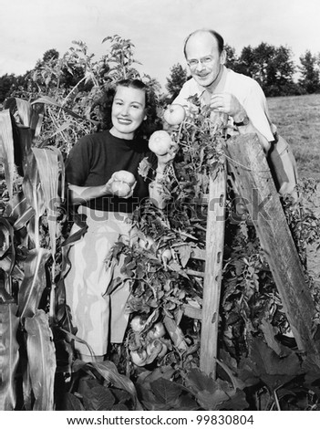Couple standing in their garden showing off tomatoes