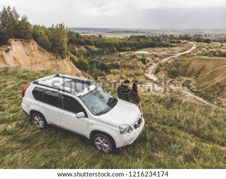 couple standing near suv car at the cliff with beautiful view from the top. overcast autumn weather
