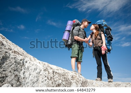 Couple standing on a cliff in the mountains