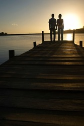 Couple standing on dock by lake holding hands back view