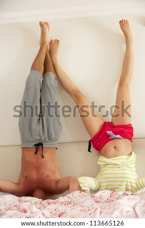 Couple Standing On Head In Bed