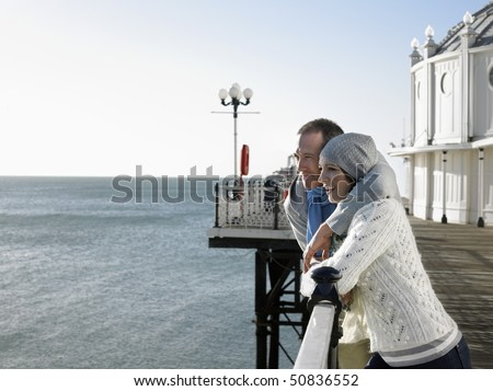 Couple standing on pier looking out at sea
