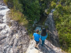 Couple standing on the edge of cliff looking down on the water