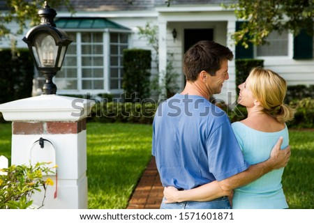 Couple standing on the garden path outside their new home