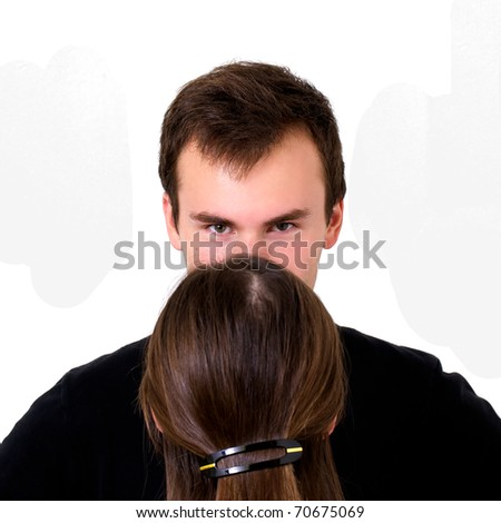 Couple standing together facing each other with husband looking over his wive's head at the camera.