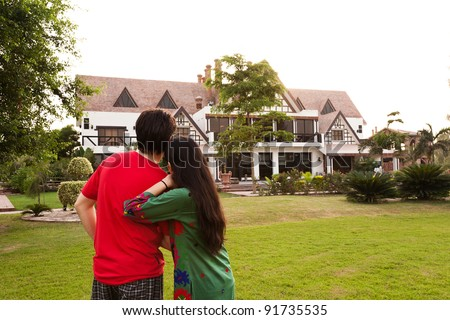 couple standing with their backs towards camera, couple standing against model house