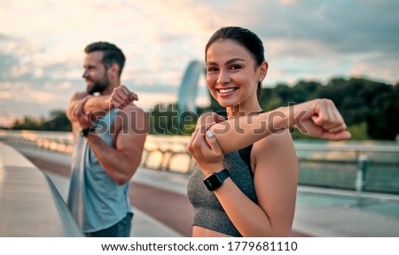 Couple stretching outdoors before morning run. Handsome bearded man and attractive sporty woman running on the street.