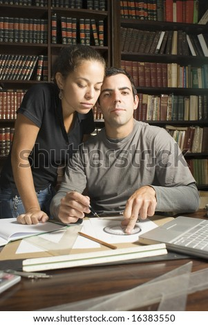 Couple studies in library. There are books and tools on the table and they are leaning against each other. Vertically framed photo.