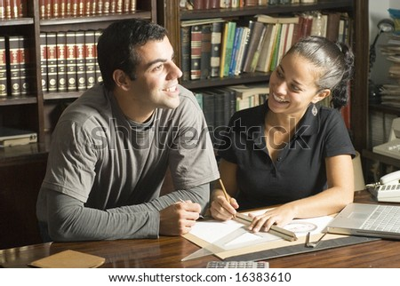 Couple studies in library. There are books and tools on the table and they are smiling. Horizontally framed photo.