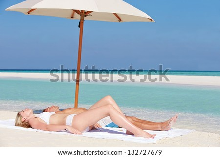 Couple Sunbathing On Beautiful Beach Holiday