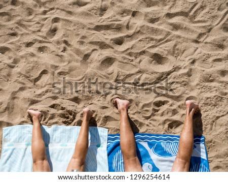 couple sunbathing on the beach #1296254614