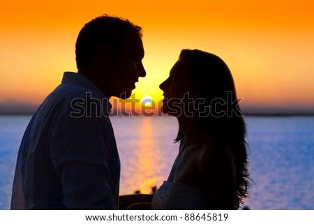 couple sunset profile back light in orange sea lake