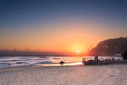 couple surfers walks along the beach in Burleigh Heads (Gold Coast, QLD, Australia)