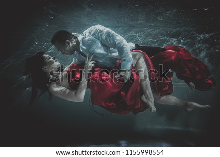 Couple swimming underwater with beautiful dress - Artistic dreamy portrait #1155998554